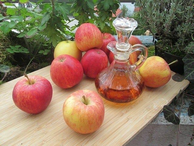 Φρέσκα μήλα και ένα μπουκάλι μηλόξυδο στο τραπέζι