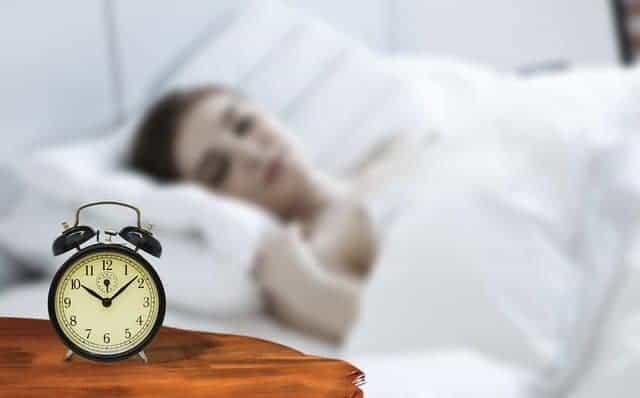 μια γυναίκα που κοιμάται με ένα ξυπνητήρι δίπλα στο κρεβάτι της