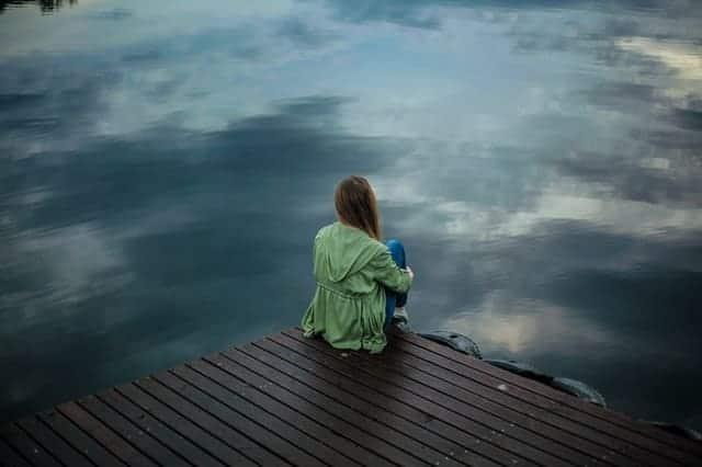 μια γυναίκα κάθεται στην άκρη μιας προβλήτας και κοιτάζει το νερό