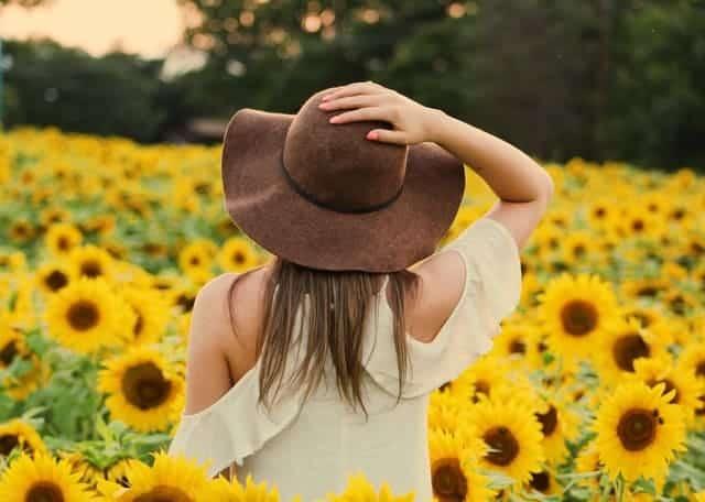 μια γυναίκα περπατά μέσα σε ένα χωράφι με ηλιοτρόπια