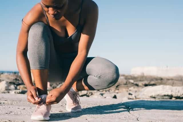 γυναίκα με αθλητική ενδυμασία δένει το παπούτσι της