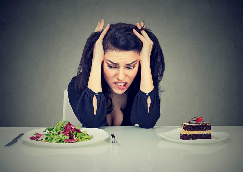 μια γυναίκα κάθεται σε ένα τραπέζι με ένα πιάτο κέικ και ένα πιάτο σαλάτα
