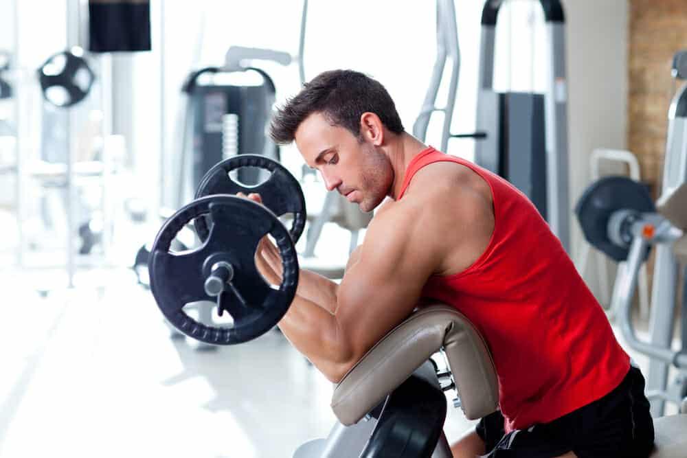 Ένας άνδρας γυμνάζεται με μια μπάρα στο γυμναστήριο.