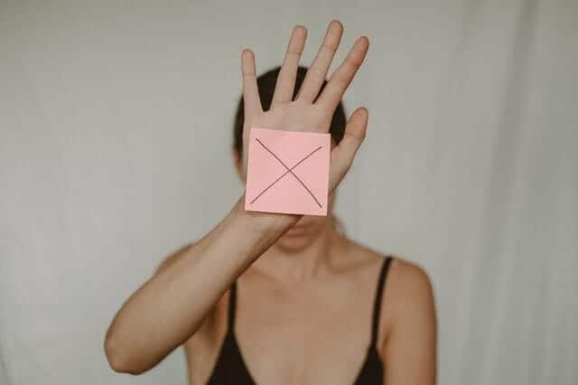 μια θλιμμένη γυναίκα κρατάει ένα χαρτόκουτο με ένα x μπροστά της
